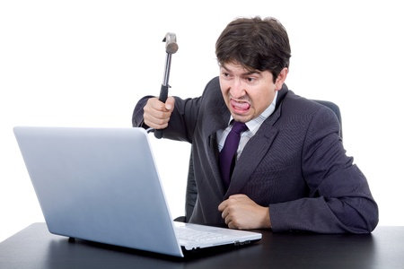 computer user: young crazy business man with a hammer smashing a laptop