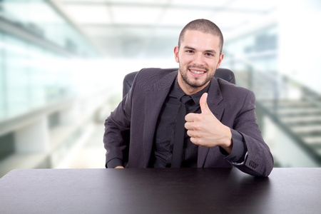young business man on a desk going thumb up photo