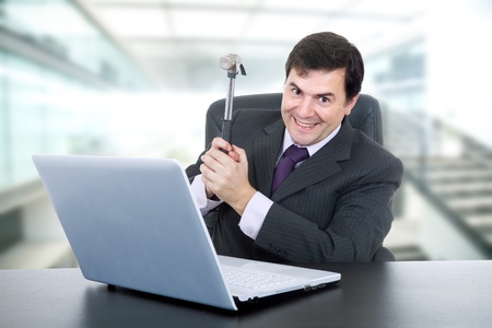 young happy business man with a hammer smashing a laptop Stock Photo - 11943999