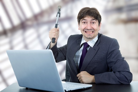 young crazy business man with a hammer smashing a laptop photo