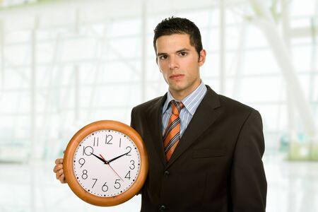 young handsome business man holding a clock photo