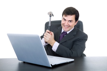 young happy business man with a hammer smashing a laptop photo