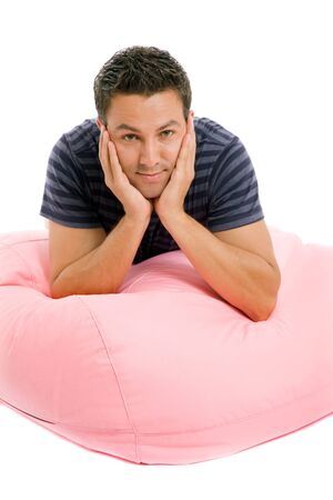 young casual man in a small sofa, studio picture Stock Photo - 14647088