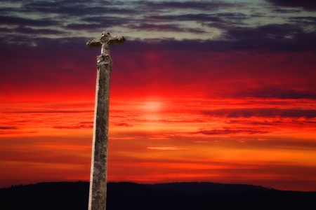 stone cross with the sunset as background photo