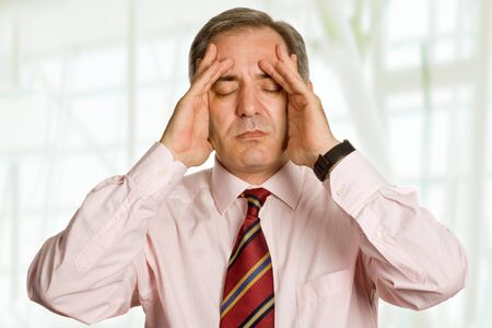 hardworker: Businessman in a suit gestures with a headache Stock Photo