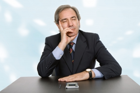 mature business man on a desk, sleeping, at the office photo