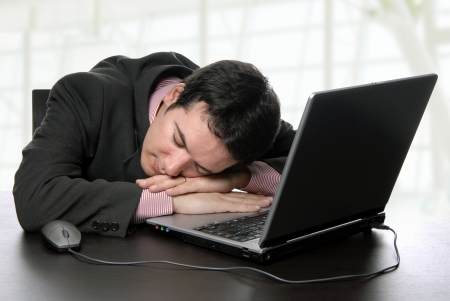 young business man sleeping on the laptop photo