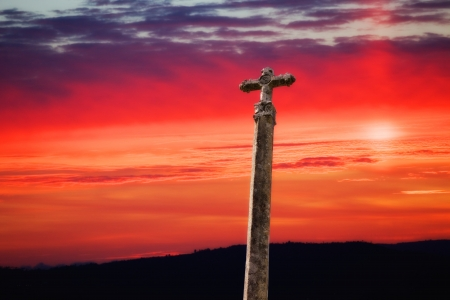 stone cross with the sunset as background Stock Photo