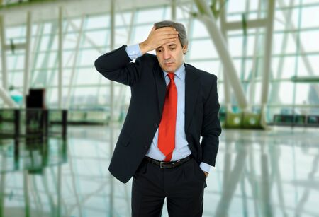 Businessman in a suit gestures with a headache photo