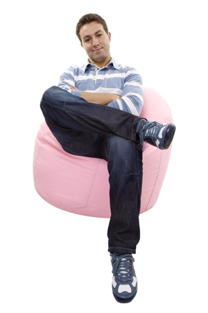 young casual man seated in a small sofa Stock Photo - 20048317