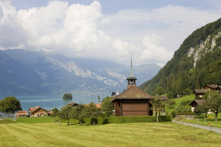View of wooden church with a lake and mountain at switzerland photo