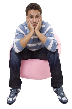 young casual man seated in a small sofa Stock Photo - 21138849