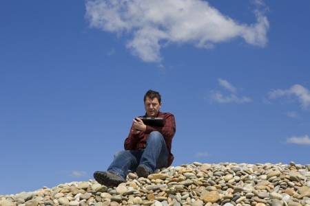 Young casual man working with touch pad at the beach photo