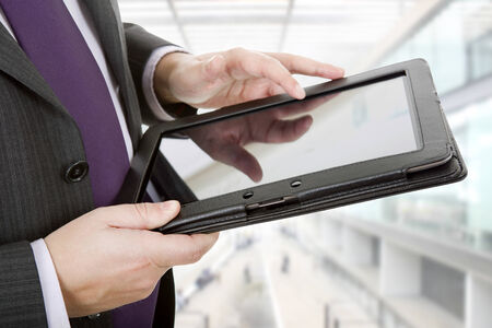 businessman using touch pad, close up shot on tablet pc, at the office photo