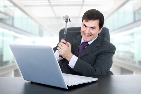 happy businessman with a hammer smashing a laptop, at the office photo