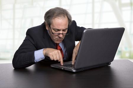 homme d'affaires mature travailler avec son ordinateur portable au bureau