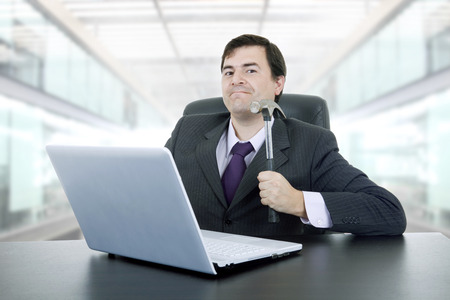 young crazy businessman with a hammer smashing a laptop, at the office photo