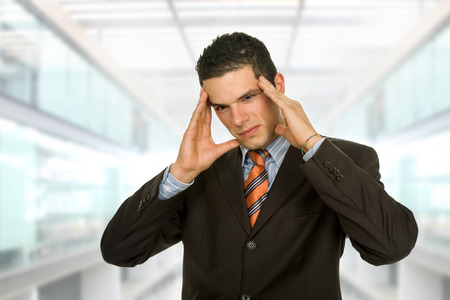 hardworker: Businessman gestures with a headache, at the office