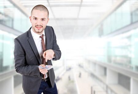 remuneraci�n: joven hombre de negocios con el dinero en la oficina