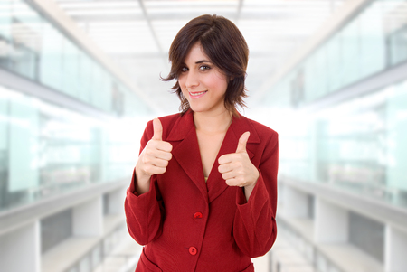 great success: young business woman portrait going thumbs up, at the office Stock Photo