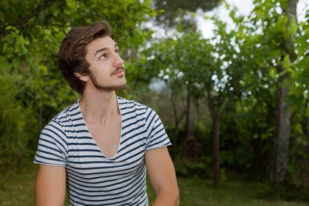 seated: young casual man seated, smiling, outdoors Stock Photo