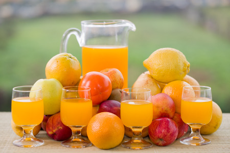 fruit juices: glasses of orange juice and lots of fruits on wooden table outdoor