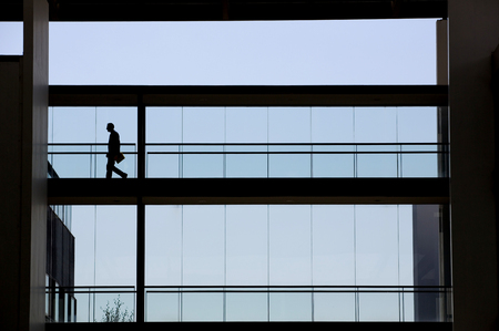 panoramic windows: Silhouette view of young businessman walking in modern office building interior with panoramic windows.