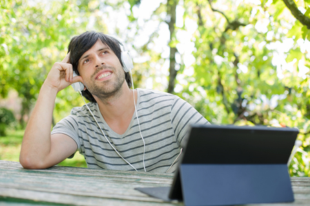 earing: young man working with a tablet pc listening music with headphones on a wooden table, outdoor