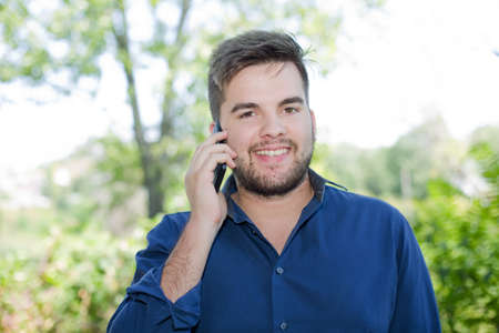 eyecontact: happy young casual man on the phone outdoor