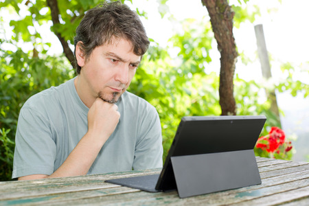 casual man working with a tablet pc, outdoor Stock Photo