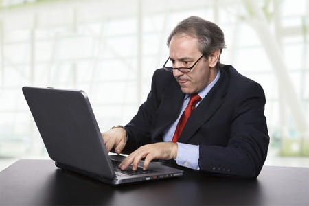mature business man working with his laptop at the office photo