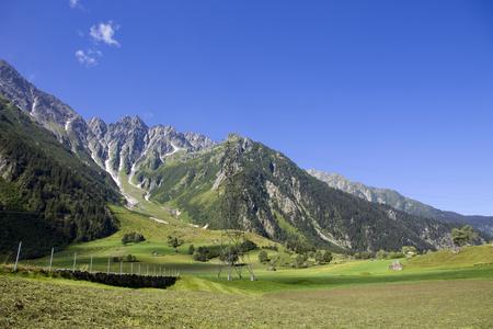 megawatt: electricity pylons crossing the Swiss Alps. Bern Canton, Switzerland Stock Photo