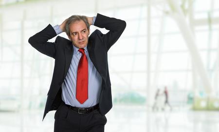 Hombre de negocios en un traje de gestos con un dolor de cabeza en la oficina Foto de archivo