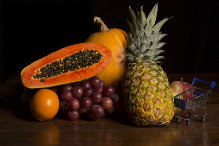woden: variety of fruits and a small shopping cart on a woden table, studio picture Stock Photo