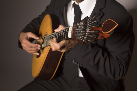 hand jamming: Close up shot of a man with his fingers on the frets of a portuguese guitar playing