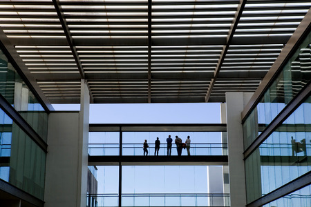 panoramic windows: Silhouette view of some people in a modern office building interior with panoramic windows. Stock Photo