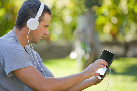 man relaxing with a tablet pc listening music with headphones on a the park, outdoor