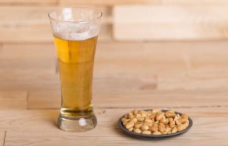 Cold beer with roasted peanuts, on wooden table, Still Life style