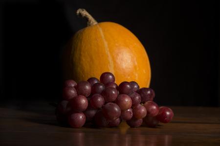 pumkin: Pumkin and grapes in the dark background, studio picture