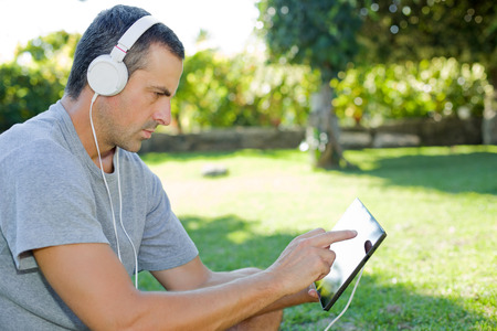 earing: young man relaxing with a tablet pc listening music with headphones on a the park, outdoor