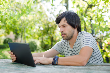 young man working with a tablet pc listening music with headphones on a wooden table, outdoor