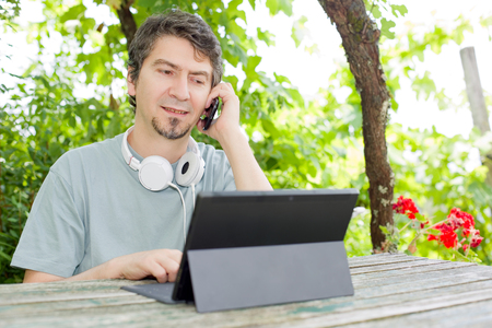 mp3 player: casual man working with a tablet pc and phone, outdoor Stock Photo
