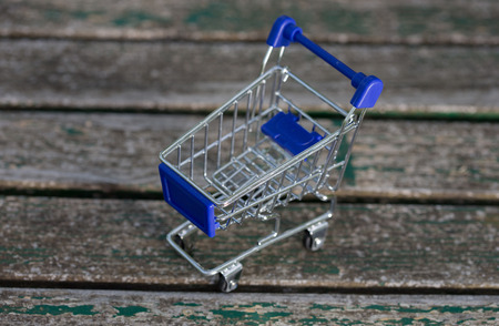 small shopping cart, on a wooden table Stock Photo