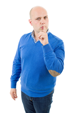 portrait of a young bald man making a shushing gesture with his finger, isolated on a white studio background. Stock Photo