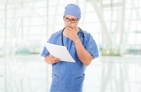 enfermera con cofia: médico preocupado mirando a sus notas, en el hospital