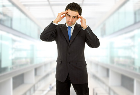 Businessman in a suit gestures with a headache at the office photo