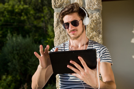 young man relaxing with a tablet pc listening music with headphones, outdoor