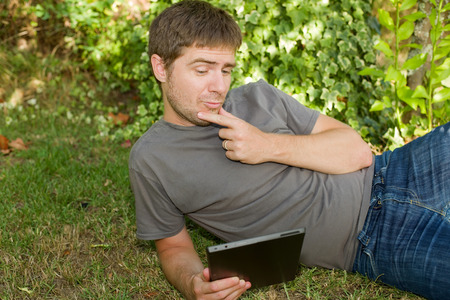 casual man working with a tablet pc, outdoor photo