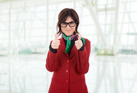 young business woman going thumbs up, at the office photo