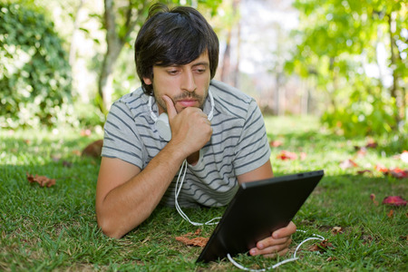 young man relaxing with a tablet pc listening music with headphones on a the park, outdoor
